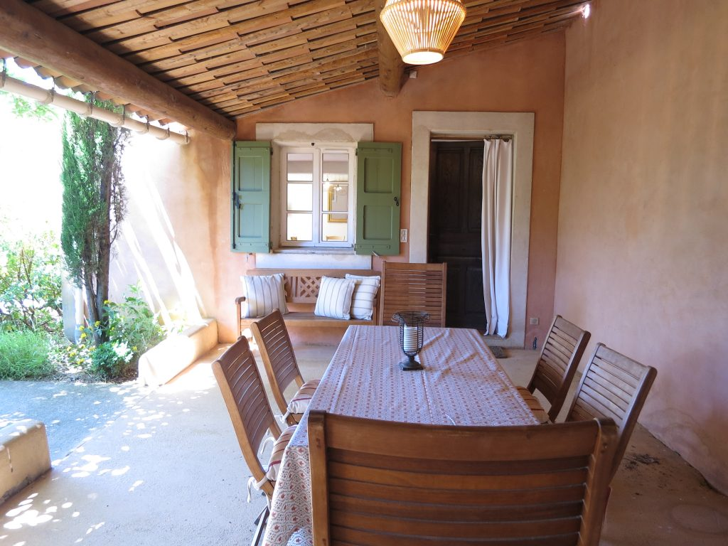 Le Mas du Luberon dispose d'une terrasse couverte aménagée avec une table pour les repas et un barbecue